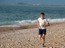 Teen jogging. Fit teenager jogging early morning on the beach Royalty Free Stock Photos