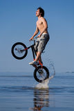 Teen jumping with the bike in water Royalty Free Stock Photo