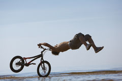 Teen jumping with the bike in water Stock Photography