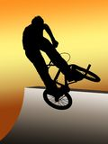 Teen jumping with bmx bike. Silhouette of jumping bmx biker on colored background Royalty Free Stock Images