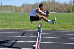 Teen jumping hurdle in a track and field event royalty free stock photos