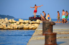 Boys jumping from a quay. Teens having fun jumping from quay in blue sea water during the summer vacation, Black sea coast, Varna, Bulgaria stock images