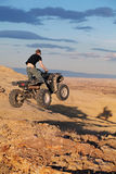 Teen jumping on quad ATV. Teenager jumping on a quad ATV in late sun - four wheeler getting air in the hills of Wyoming Stock Photo