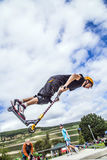 Teen jumps with scooter over a ramp and performs a salto Royalty Free Stock Images