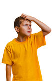 Teen kid boy blonde in yellow shirt scratching his Royalty Free Stock Photos