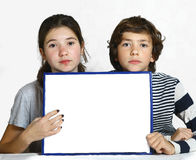 Teen kids boy and girl hold blank paper sheet. Sad teen kids boy and girl hold blank paper sheet in frame close up portrait royalty free stock images