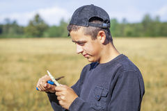 Teen with a knife cuts the branch on the field Royalty Free Stock Images