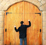 Teen knocking door. Teen knocking wooden old door in Cyprus Stock Image