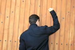 Teen knocking the door. Teen knocking the wooden old door.Cyprus,Limassol Stock Photo