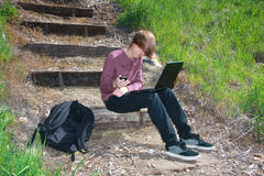 Teen with Laptop and Phone. Smiling teenaged boy sitting on outdoor steps with laptop on lap, phone in hand and backpack nearby Royalty Free Stock Images
