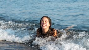 Teen laying on her stomach at beach laughing royalty free stock images