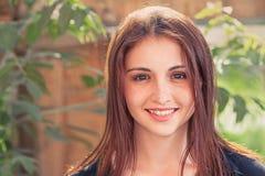 Teen le redhead Closeupbild för främre sikt av en le tonårs- flicka utomhus mot gammal wood plankabakgrund med sidor Royaltyfri Foto