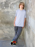 Teen Leaning on Wall. Cute teen boy leaning against a cement wall Stock Image
