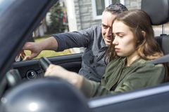 Teen learning to drive or taking driving test. Royalty Free Stock Photography