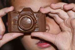 Teen learns to take pictures and holds in hands a camera made of chocolate, a sweet New Year gift, black background stock photos