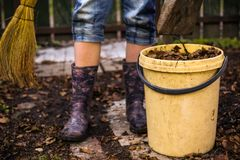 Teen leg with rubber floral boots broom and bin with old dry leafs. Close up country spring photo royalty free stock images