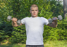 Teen lifting dumbbells outdoors royalty free stock image