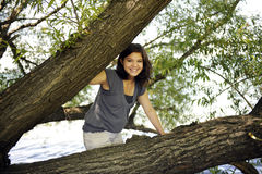 Teen between the Limbs. A pretty teen girl climbing among the thick limbs of tree fallen over a lake Royalty Free Stock Photo