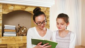 Teen listening how her sister reading story, girls spending time after book reading, family idyll stock video