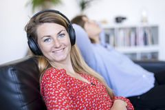 Teen listening music with headphones and looking at you sitting royalty free stock photography