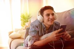 Teen listening music with headphones lying face down multicolore. Teen listening music with headphones from mobile lying face down on couch multicolored lights Stock Images