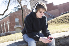 Teen listening music and looking at phone. A teen listening music and looking at phone Royalty Free Stock Photography
