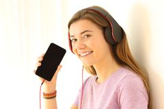 Teen listening music and showing a smart phone screen. Portrait of a happy teen listening music and showing a blank smart phone screen isolated at side Stock Photo