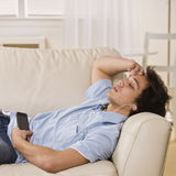Teen listening to ipod. With eyes closed on the couch. square Stock Photos