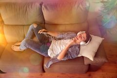 Teen listening to music and dancing on couch top view. Teenager listening to music with headsets from a smartphone and dancing face up on couch in the living Royalty Free Stock Photo