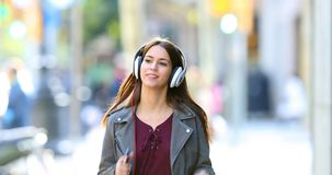Teen listening to music dancing in the street. Front view of a happy teen listening to music dancing in the street