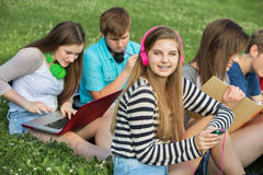 Teen Listening to Music. Happy teen with male and female friends outdoors Royalty Free Stock Photography