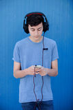 Teen listening to music with headphones. On blue background Royalty Free Stock Photo