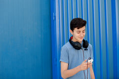 Teen listening to music with headphones. On blue background Stock Images