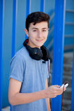 Teen listening to music with headphones. On blue background Royalty Free Stock Photography