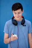 Teen listening to music with headphones. On blue background Stock Photos