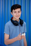 Teen listening to music with headphones. On blue background Royalty Free Stock Photos