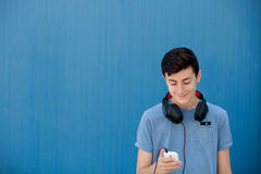 Teen listening to music with headphones. On blue background Royalty Free Stock Image