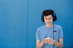 Teen listening to music with headphones. On blue background Royalty Free Stock Images