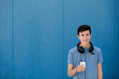 Teen listening to music with headphones. On blue background Stock Photo