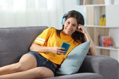 Teen listening to music looking at camera at home. Happy teen listening to music looking at camera lying on a couch in the living room at home stock images