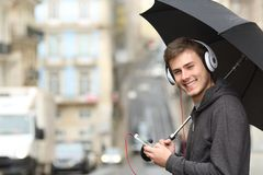 Teen listening to music looking at you. Happy teen listening to music wearing headphones looking at you in the street under the rain Stock Photography