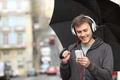 Teen listening to music with a phone under the rain. Happy teen listening to music with a smart phone and headphones under the rain in the street Stock Image