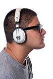 Teen Listening to Music. A young man listens to music with a set of head phones over a white background Royalty Free Stock Image