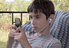Teen listens youth music through headphones. Teen 11-12 years listens youth music through headphones mobile phone Royalty Free Stock Photography