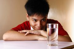 Teen looking at a glass of water on a wooden table Royalty Free Stock Image