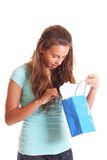 Teen looking inside gift bag Royalty Free Stock Photos