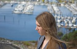 Teen Looking Sideways Over Marina. This pretty teen is looking sideways at scene overlooking a marina with her hair blowing in the wind slightly Royalty Free Stock Photos