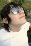 Teen Looking Up. A young male teen looking upwards wearing sunglasses that reflect the clouds and skies above. Has a slight smile on his face and a confident Royalty Free Stock Photos