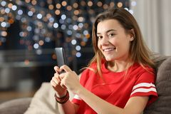 Teen looking at you holding a phone in the night. Sitting on a couch in the living room at home Stock Photo