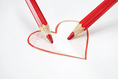 School love. Two red pencils colouring together a heart drawn Stock Image